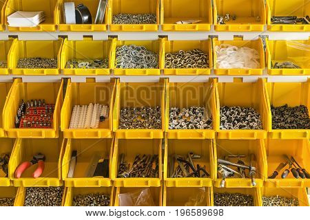 Lot of plastic yellow boxes are hanging on the light wall in the workshop. Inside them there are screws, nuts, dowels, drillers, lines, pliers, nozzles, insulating tapes, etc. Closeup. Horizontal.