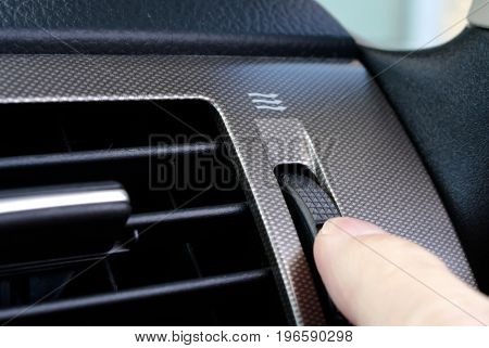 A woman's hand adjusts the vent on car dashboard