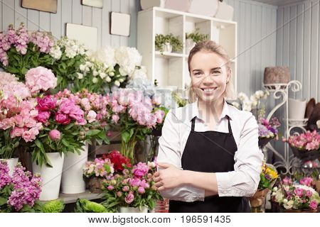 Beautiful young florist in flower shop
