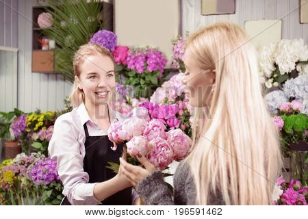 Young woman buying peonies in flower shop