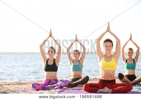 Group of young women practicing yoga outdoors