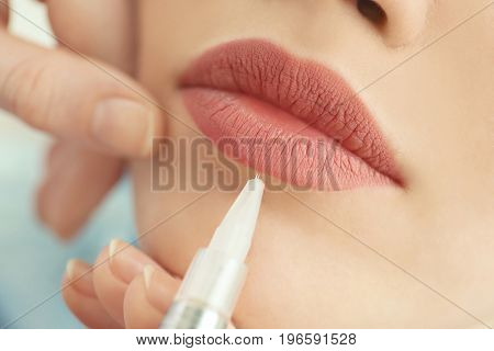 Young woman having permanent makeup on lips in beautician salon, closeup