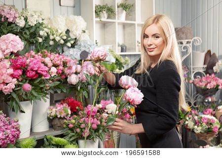 Beautiful female florist making bouquet of peonies in flower shop