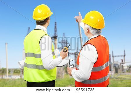 Engineers and electric substation on background