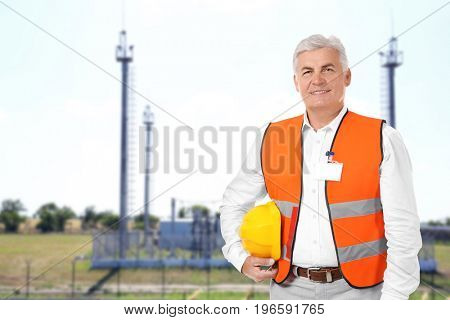 Senior engineer and electric substation on background