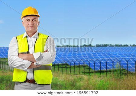 Senior engineer and solar panels on background