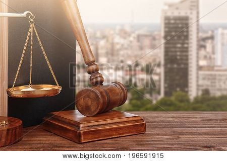 Judge's gavel with book and scales on cityscape background, closeup. Concept of law