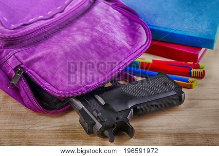 Backpack with gun on table, closeup. School shooting concept