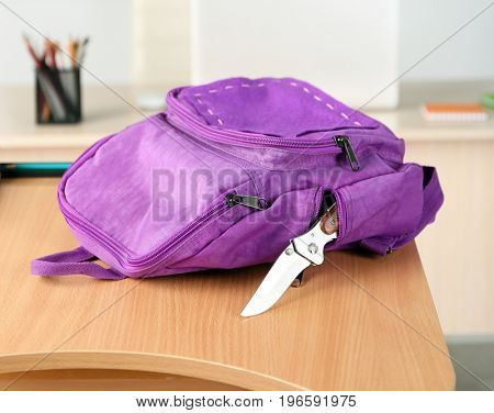 Backpack with knife on table in classroom at school
