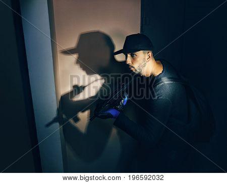 Terrorist with gun in hall near classroom at night. School shooting concept