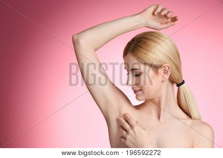 Beautiful young woman on color background. Concept of using deodorant