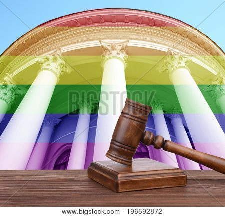 Judge's gavel and courthouse with colors of gay flag on background. LGBT rights concept