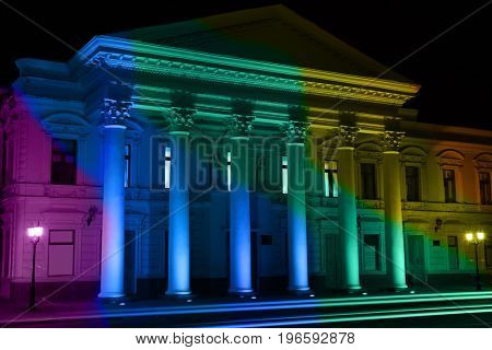 Courthouse with illumination of gay flag colors at night. LGBT rights concept
