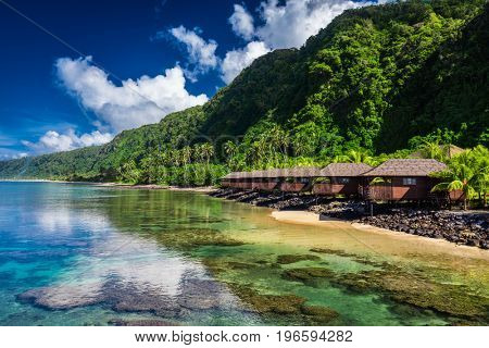 Tropical beach with with coconut palm trees and beach houses on Samoa, Upolu Island