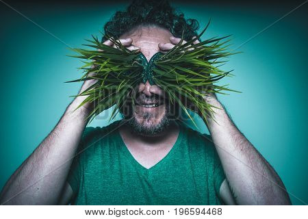 Concept of addiction to drugs, man with grass in eyes with gesture of happiness