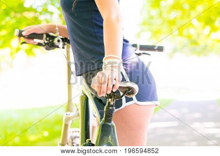Young slim woman standing next to bicycle