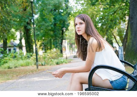 Young smiling woman with long hair in summer park sits on a bench and use smartphone