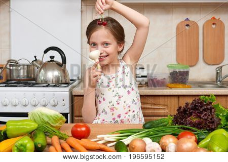 child girl with fruits and vegetables in home kitchen interior, healthy food concept, hold garlic in hands