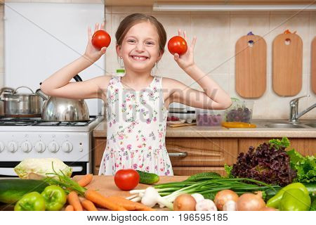 Child girl having fun with tomatoes and carrot. Home kitchen interior with fruits and vegetables. Healthy food concept