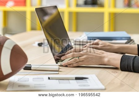 Specialist is using a laptop on wooden table on the blurry background of the yellow shelves in the office. Next to her there are football ball, markers and pencils, papers, book. Closeup. Horizontal.