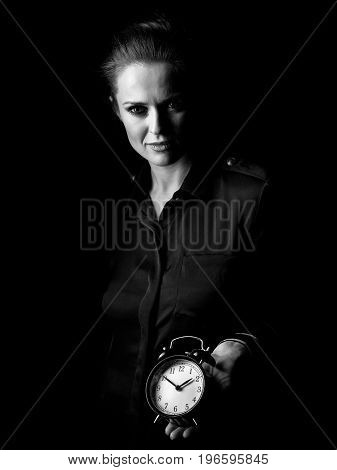 Woman In Dark Dress Isolated On Black Showing Alarm Clock