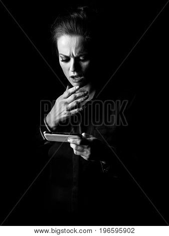 Stressed Woman In Dark Dress Isolated On Black Reading Sms