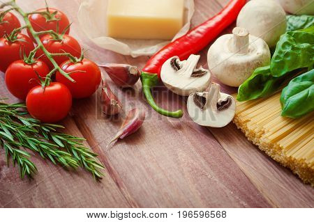 bunch of Italian spaghetti closeup with mushrooms and tomatoes on a rustic kitchen on a wooden table. In background mode, chef chopped tomatoes for cooking Spaghetti