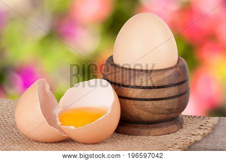 eggs on a wooden board with blurred garden background.