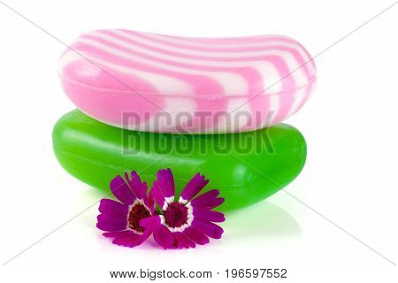 Two multi-colored striped soaps with a flower isolated on white background.