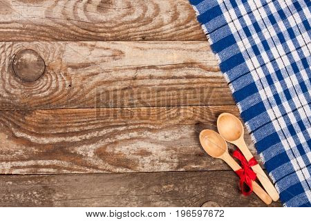 blue checkered tablecloth on the old wooden table with copy space for your text. Top view.