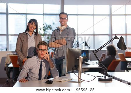 Portrait of young business people discussing business plan  in the office