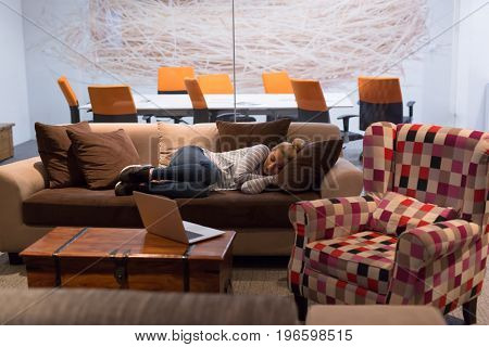 A young casual business woman sleeping on a sofa during a work break in a creative office