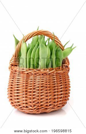 Green beans in a wicker basket isolated on a white background.