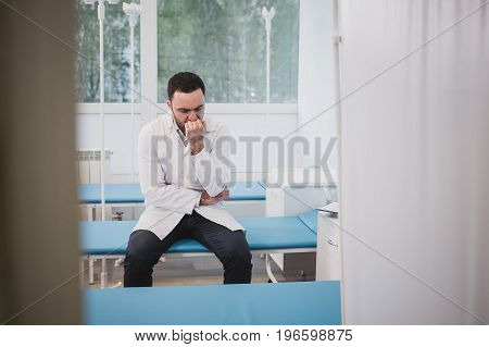Handsome young doctor in white coat is sitting sadly in hospital ward.