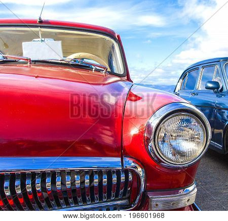 Russia Kamchatka - 05 October 2017: Red vintage car GAZ-21 on a festival of old cars on Kamchatka. Retro car's headlight close up.