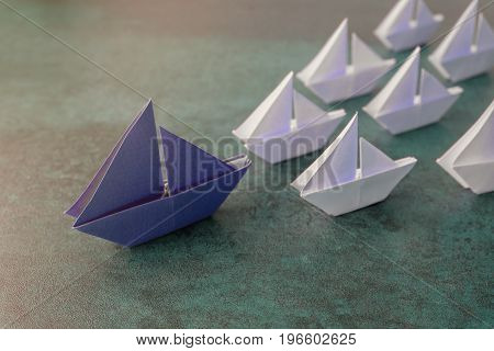 Origami paper sailboats leadership business concept toning