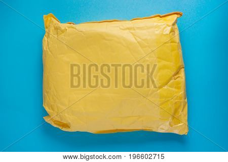 Yellow postal cardboard package on blue background. Copy space on the package