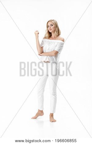 Beautiful serious blond woman in a white blouse and pants on a white background