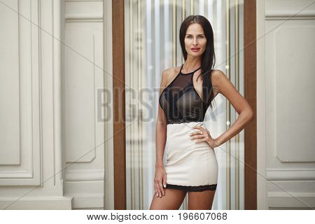 Sexy young model. Portrait close up of young beautiful brunette woman in beige dress, indoor