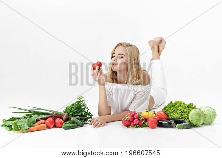 Beautiful blond woman in white clothes and lots of fresh vegetables on a white background. Girl holding a tomato