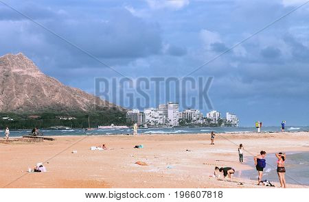 Honolulu, Hawaii, USA - May 30, 2016: People enjoying the beach at Ala Moana Magic Island with Waikiki and Diamond Head in the background.