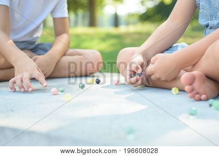 Kids playing marbles game outside on bright sunny day, having fun together at summer break. Children activities.