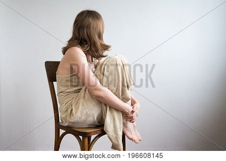 Beautiful woman in an evening gown sitting on a wooden chair, hugging her knees, her face turned away from the viewer.