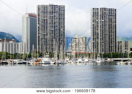 Honolulu Hawaii USA - May 30 2016: Yachts docked at Ala Wai Boat Harbour in the Kahanamoku Lagoon with high rise buildings in the background.