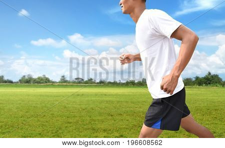 Man running on asphalt road to training