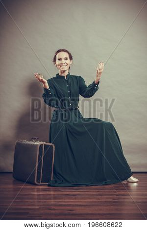 Woman retro style long dark green gown with old suitcase vintage photo
