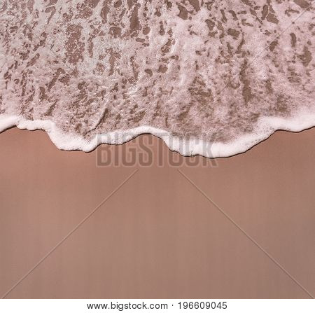 Top view of the wave of the sea invading the sand of the beach.
