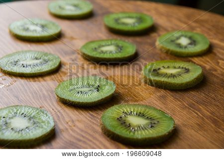 Green Slices Of Kiwi Fruit On Wood Cutting Board