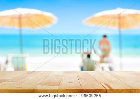 Wood table top on blurred beautiful white sand beach background with some people - can be used for montage or display your products