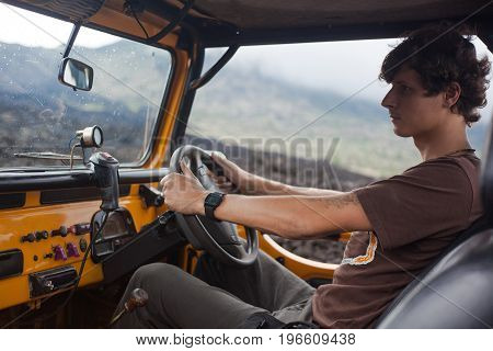A close shot of a curly-haired tatooed man in brown T-shirt is looking through a mirror and sitting at the weel in the offroad yelow vehicle parked at top of a valley with volcanic rock in Bali